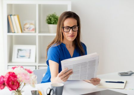 woman in glasses reading newspaper at office